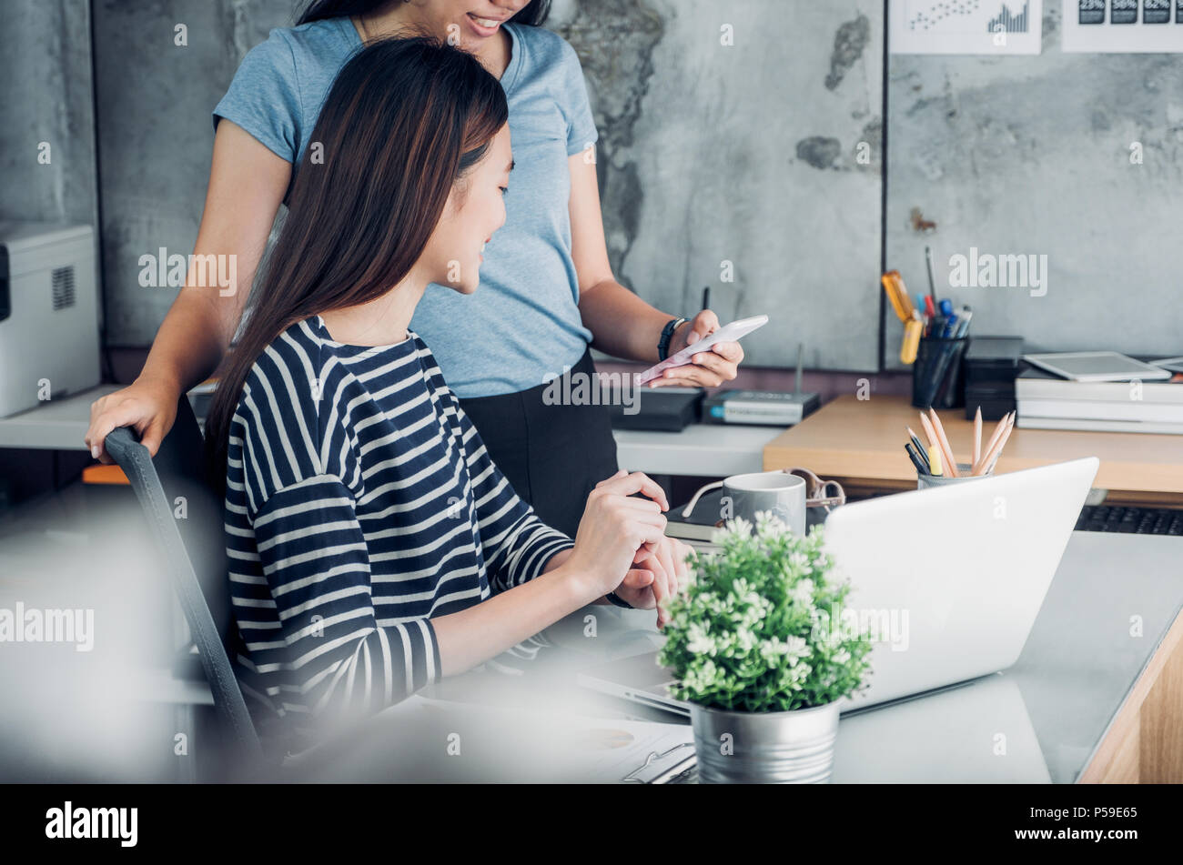 Two asian woman colleagues causal meeting at home office. discuss about business planing at laptop,business teamwork, work mate consulting together - Stock Image