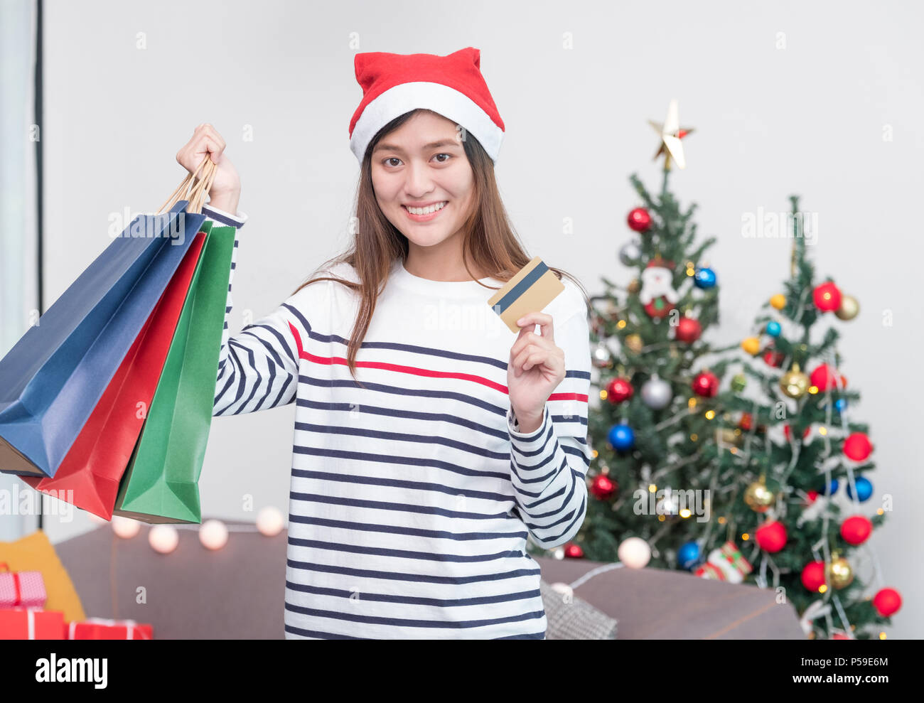 Happy Asia woman use credit card buy Christmas gift in shopping bag ...