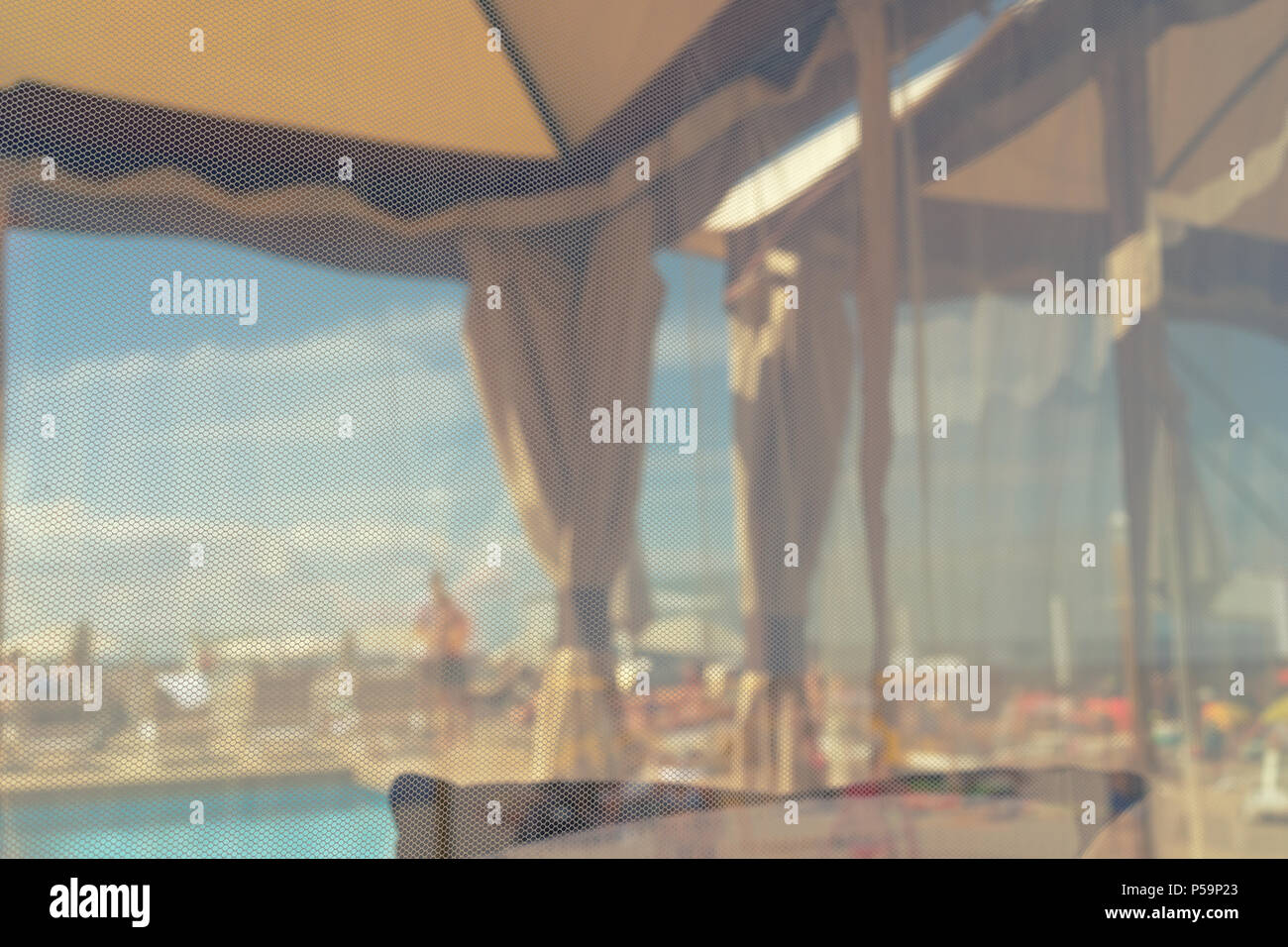 A closed beach by the sea with a swimming pool is a place of rest on a sunny summer day through a translucent curtain. Blurry - Stock Image