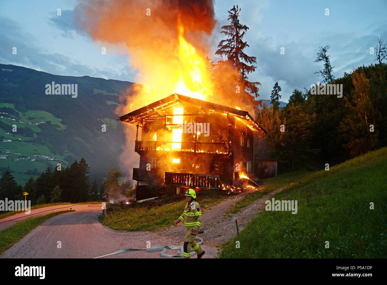 Austria, Ramsau. 26th June, 2018. The fire department attempts to extinguish the fire burning a wooden house in the Austrian Zillertal valley. The house which a German family had rented for a longer time period burned down completely. Credit: zillertalfotos.at/Jürgen Masching/dpa/Alamy Live News - Stock Image