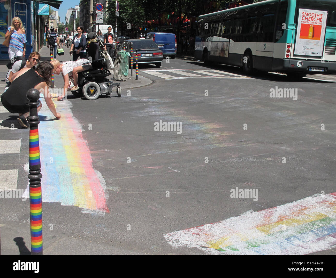 Paris, France. 26th June, 2018. Pedestrians draw a rainbow with chalk beside another rainbow, which was covered covered with paint at a street crossing. Shortly before a so-called pride parade in Paris, a homophobic gesture, in which rainbows were covered with paint, led to protests. The capital city is now planning to react by colouring additional sections. Credit: Ronja Bauer/dpa/Alamy Live News - Stock Image