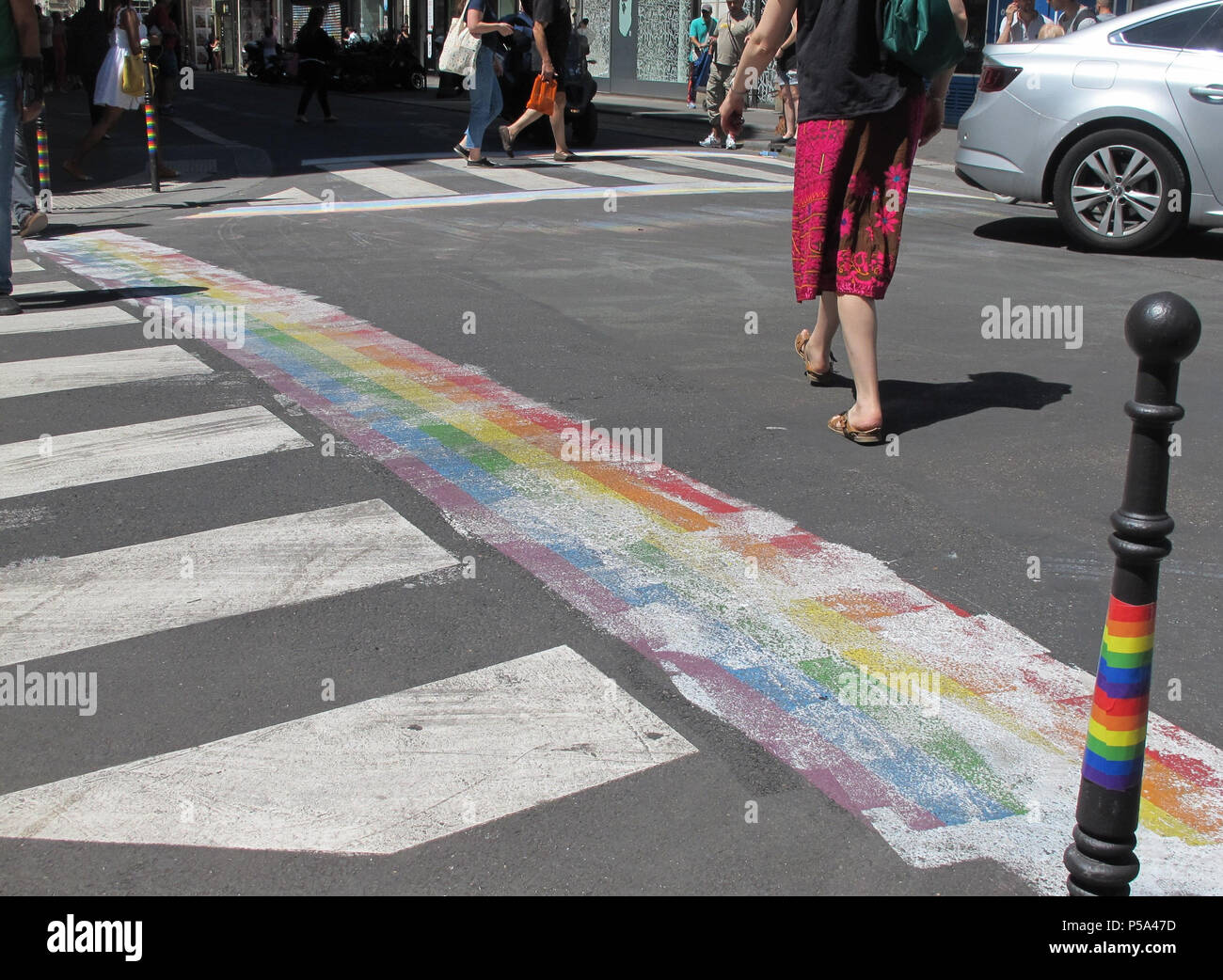 Paris, France. 26th June, 2018. A woman walks along a rainbow, which was covered with paint at a street crossing. Shortly before a so-called pride parade in Paris, a homophobic gesture, in which rainbows were covered with paint, led to protests. The capital city is now planning to react by colouring additional sections. Credit: Ronja Bauer/dpa/Alamy Live News - Stock Image