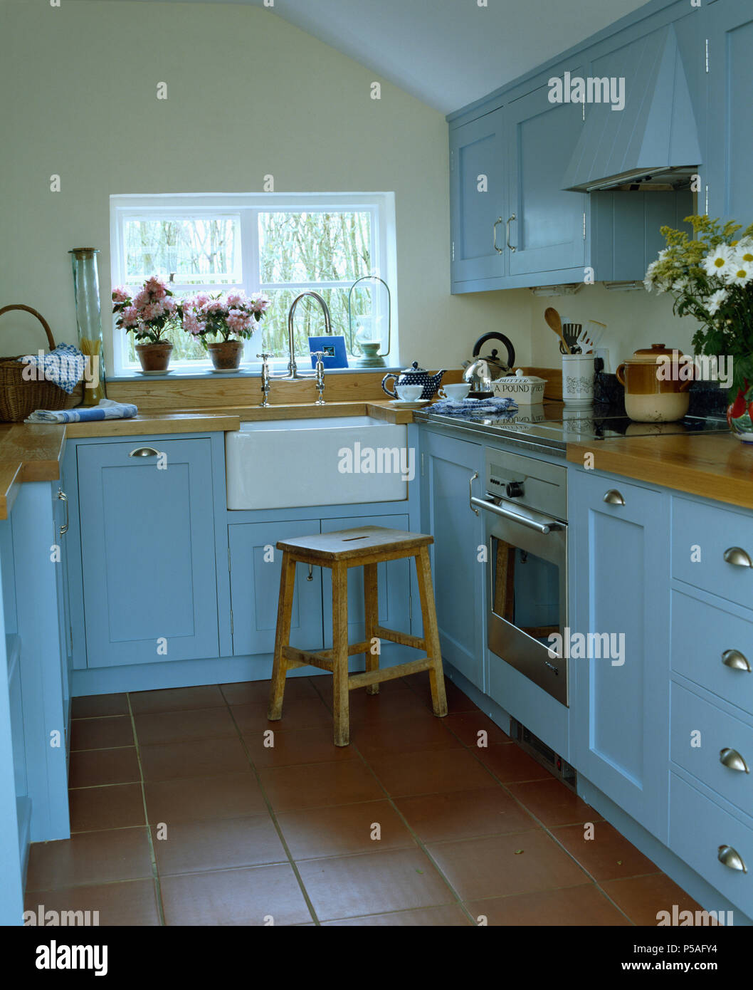 Small cottsage kitchen with pale blue units and quarry tiled floor ...