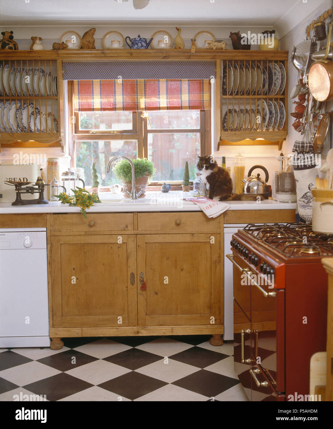 Wooden plate-racks either side of window with red blind above sink in cottage kitchen with black+white chequer-board floor - Stock Image