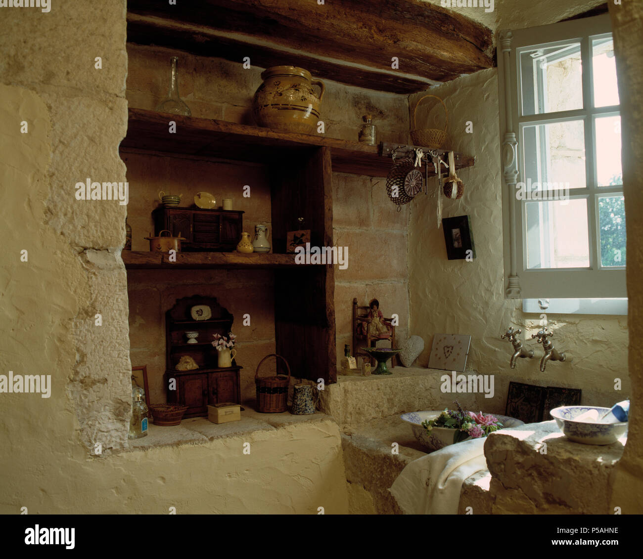 Wooden Shelves In Alcove In Old French Country Kitchen With Stone
