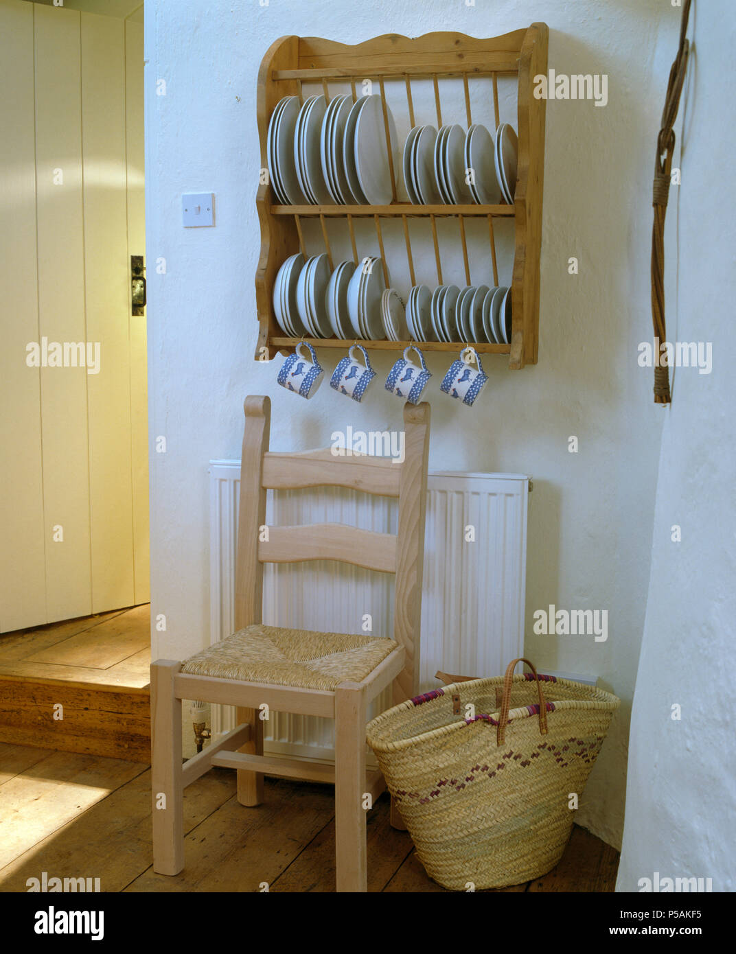 White plates on pine plate rack above rush seated chair and raffia basket incottage kitchen with raffia basket & White plates on pine plate rack above rush seated chair and raffia ...