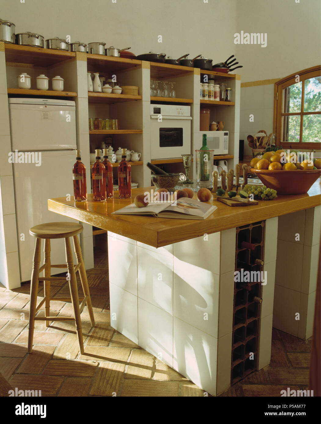Bottles of oil on wooden worktop of island unit in Greek coastal kitchen with brick flooring - Stock Image