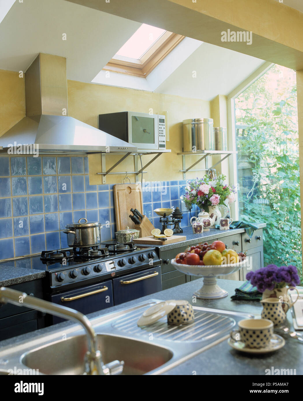 Stainless Steel Sink In Modern Kitchen Extension With Blue Wall
