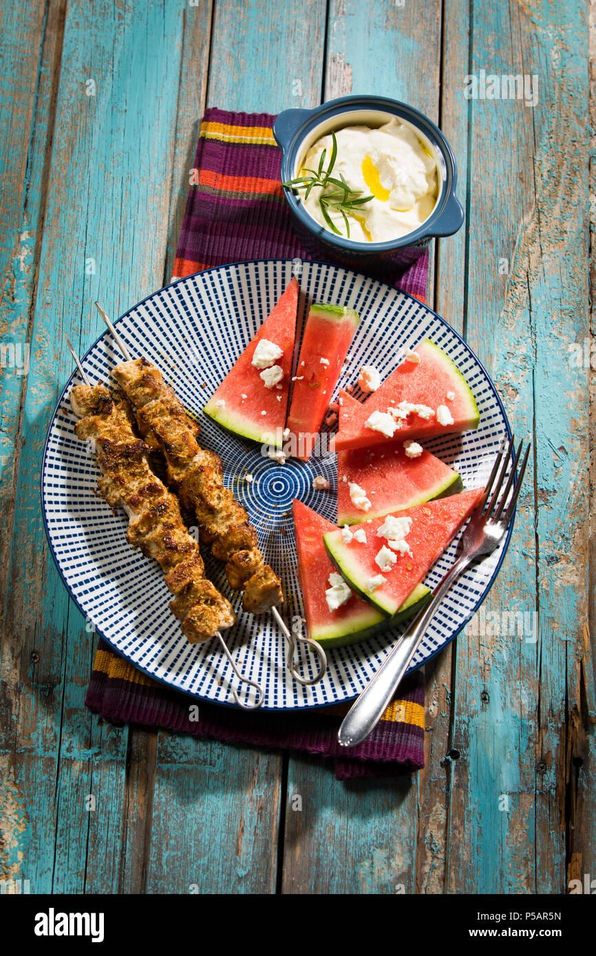 Souflaki - 2 gegrillte Schweinespieße mit Wassermelone, Feta und Knoblauch-Creme - Stock Image