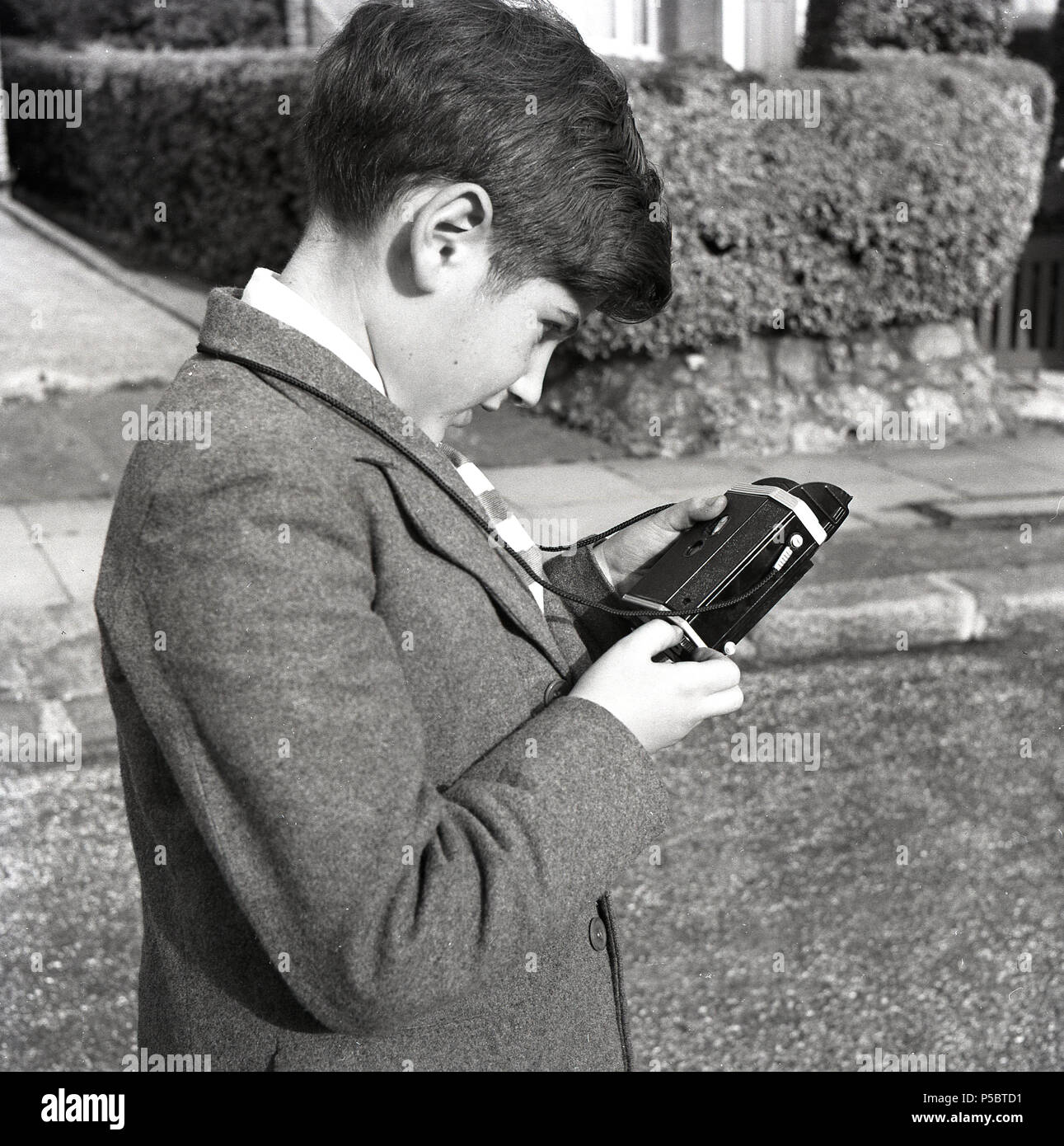 1950s, historical, young schoolboy outside checking the back of his Kodak Brownie camera to see how many photos he has left on the roll of film. - Stock Image