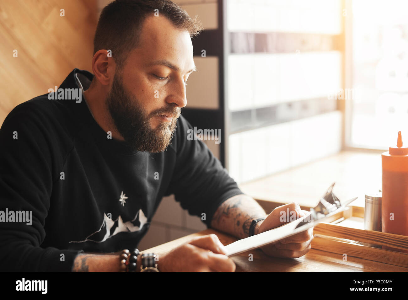 Young tattooed man holding menu at cafe, side view. - Stock Image