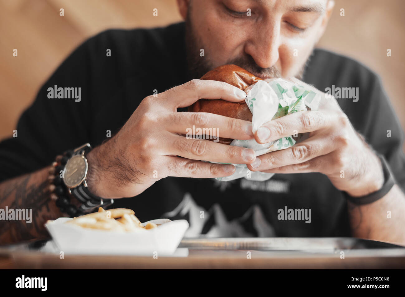 Young bearded man eating burger. - Stock Image