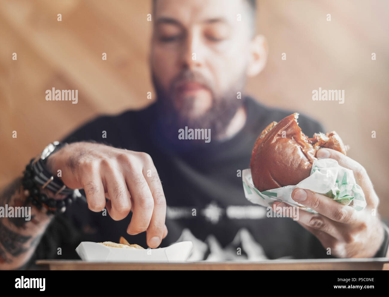 Young bearded man eating burger and french fries. - Stock Image