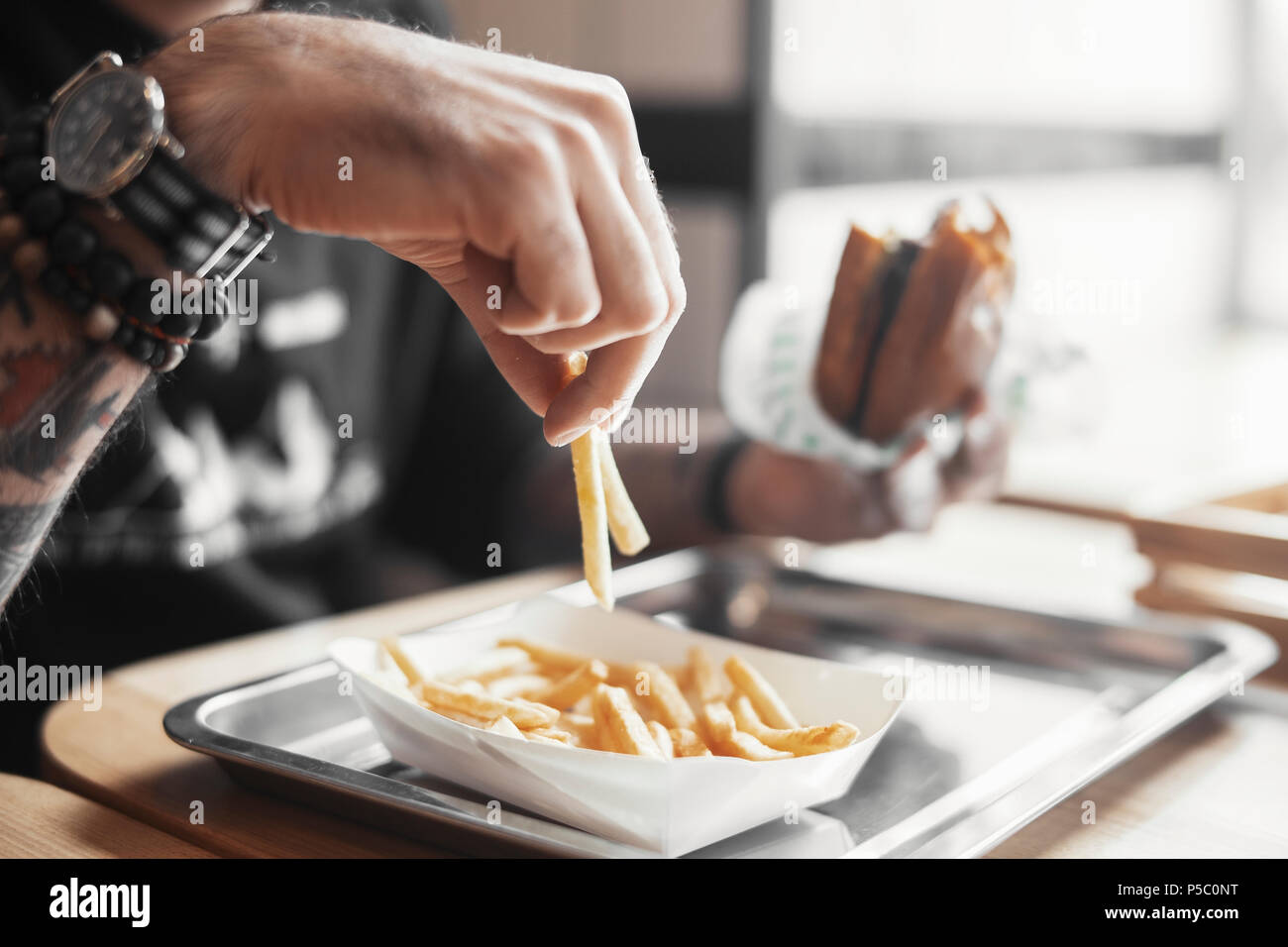 Young bearded man eating burger and french fries close up. - Stock Image