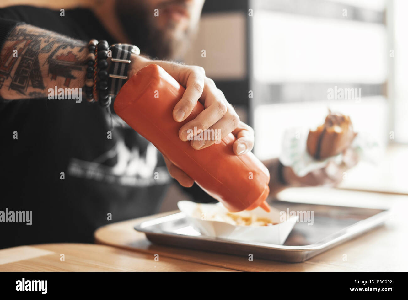Young bearded man pours ketchup on french fries close up. - Stock Image