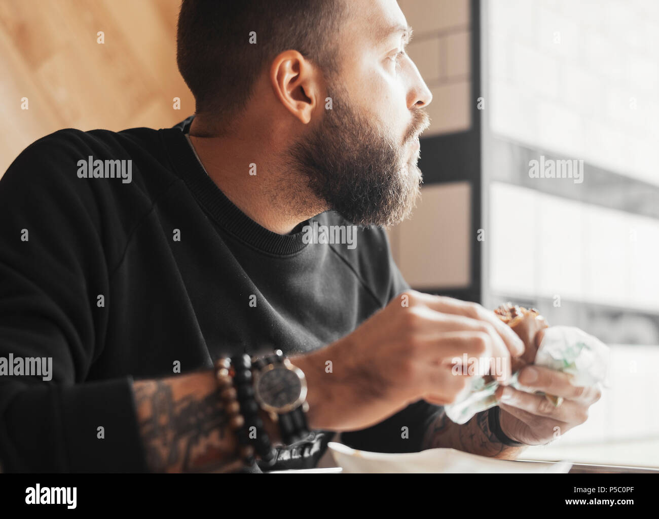 Young bearded man eating burger close up. - Stock Image