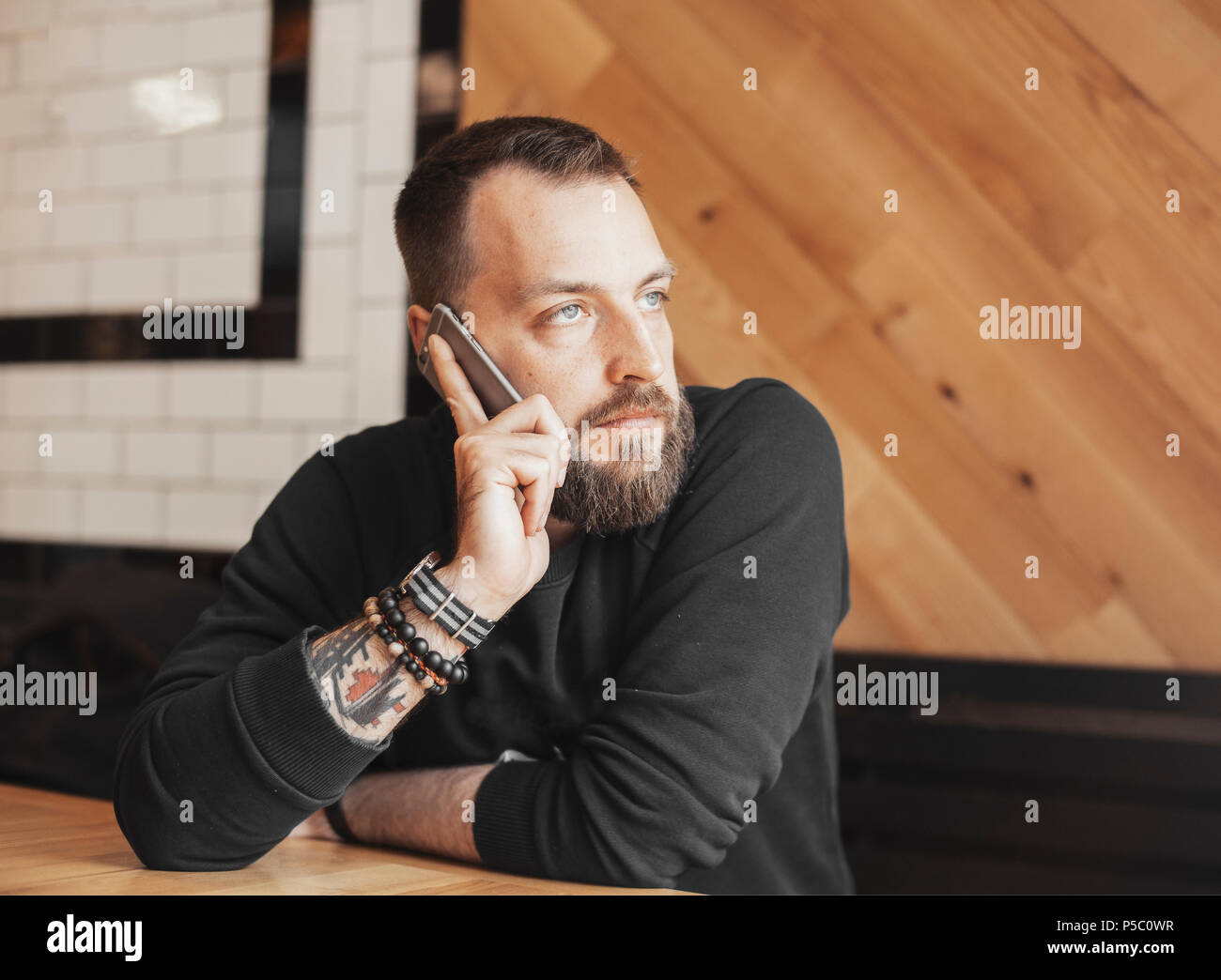 Bearded attractive tattooed man talking by phone in cafe. - Stock Image