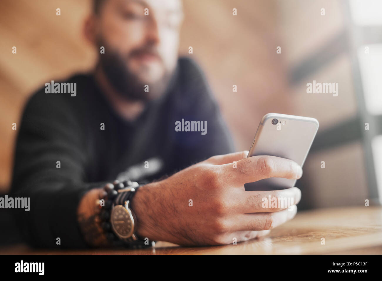 Young tattooed man holding mobile phone in right hand close up. Stock Photo