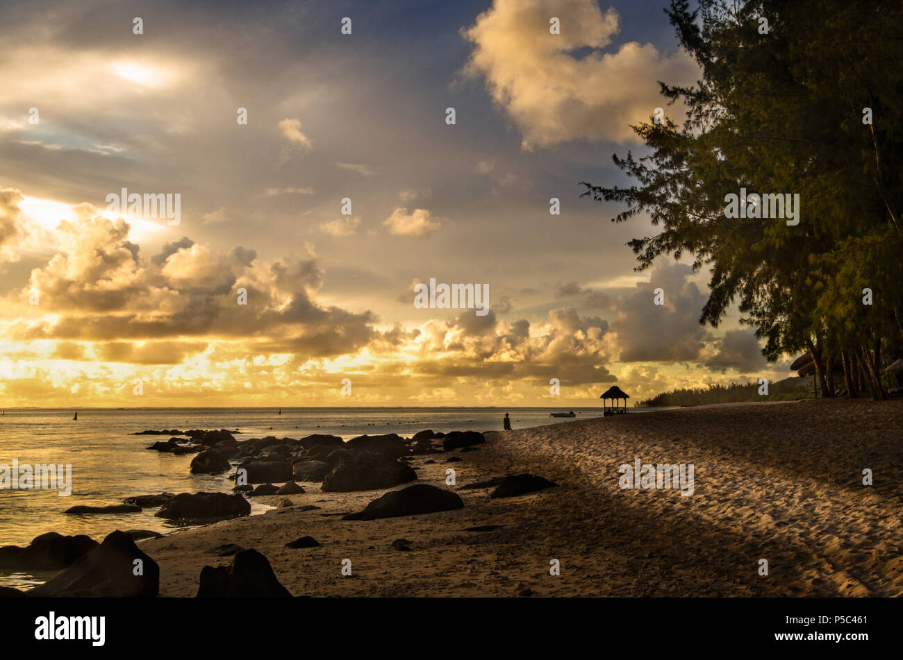 A golden sunset on the beach on Bel Ombre in Southern Mauritius,Africa, creating a tranquil and meditative environment with last sunshine on the beach - Stock Image