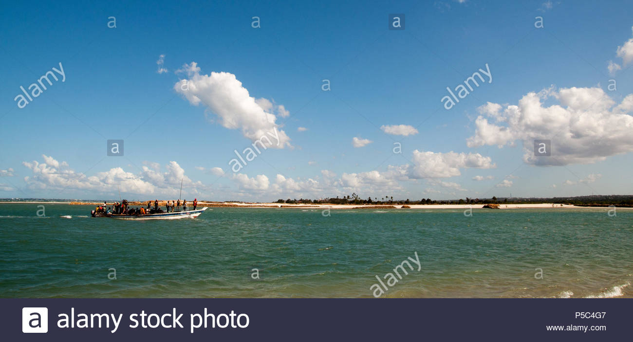 A local ferry bringing Tanzanian people  to Dar es Salaam from nearest islands through Indian Ocean in a picturesque background of dramatic clouds - Stock Image