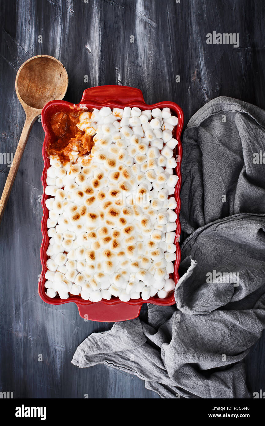 Sweet Potato Casserole baked with mini marshmallows ready for Thanksgiving Day. A piece missing from corner. Shot from above. Stock Photo