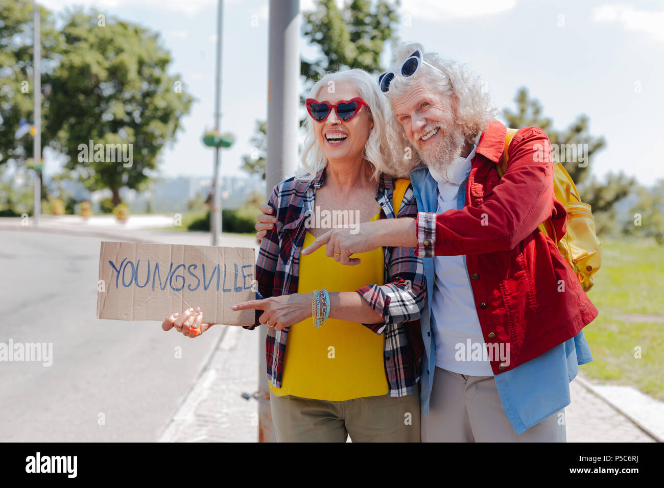 Positive aged man pointing at the sign - Stock Image