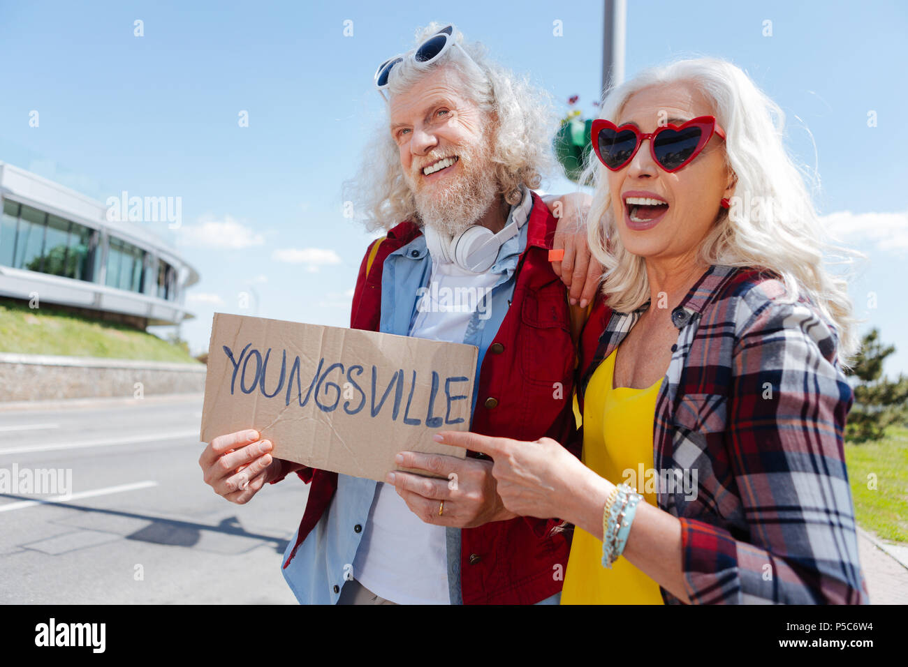 Joyful elderly couple looking for a ride - Stock Image