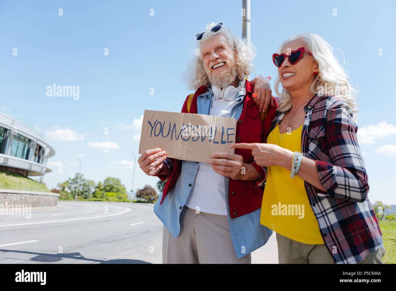 Delighted aged woman pointing at the sign - Stock Image