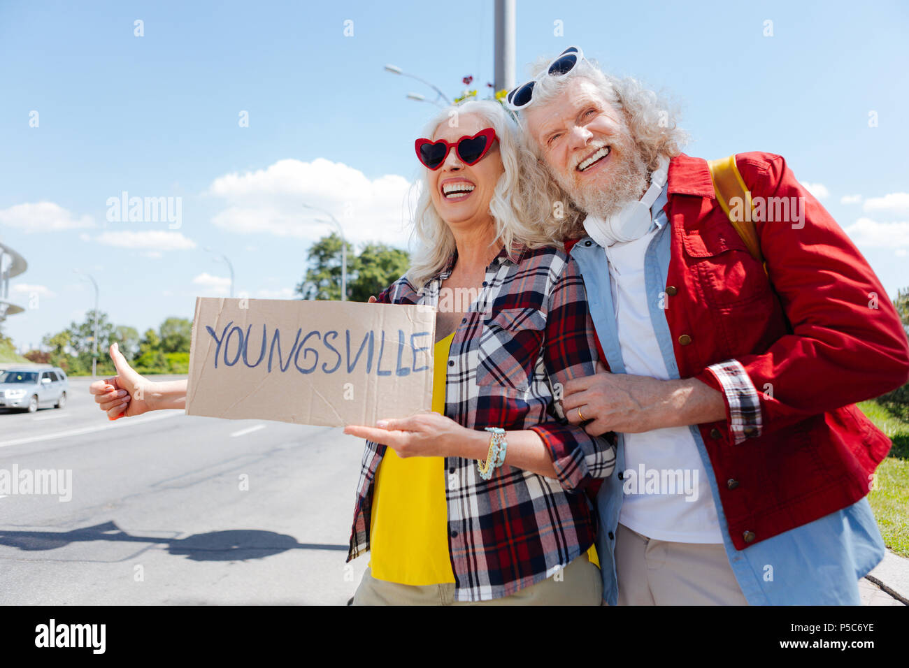 Delighted positive couple hitchhiking - Stock Image