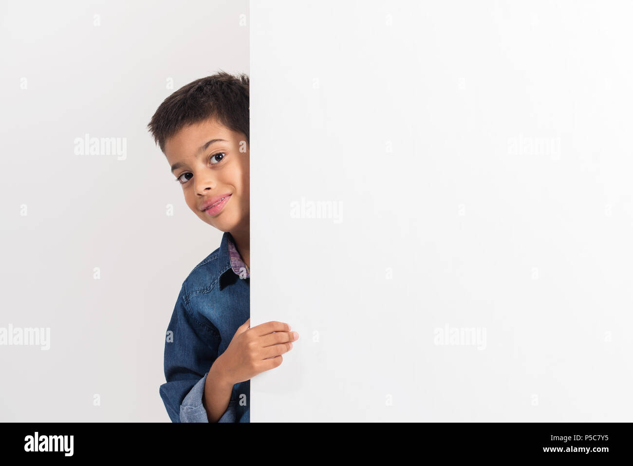 Portrait of a happy little boy holding a blank board against white background. - Stock Image