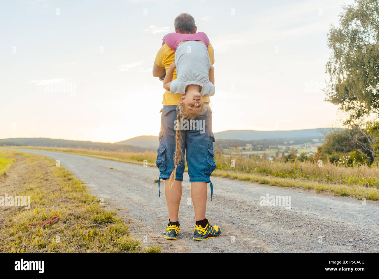 Father carrying his daughter piggyback in summer - Stock Image