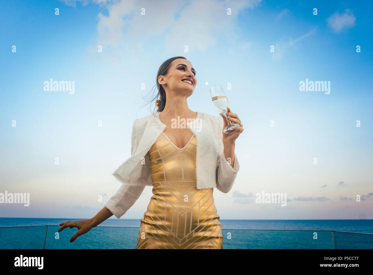 Woman sitting by the sea at a party on beach Stock Photo