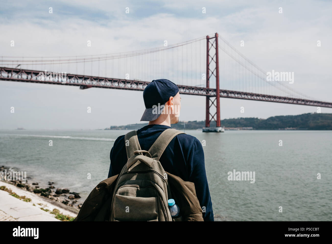 A young traveler or a tourist with a backpack on the waterfront in Lisbon in Portugal next to the 25th of April Bridge - Stock Image