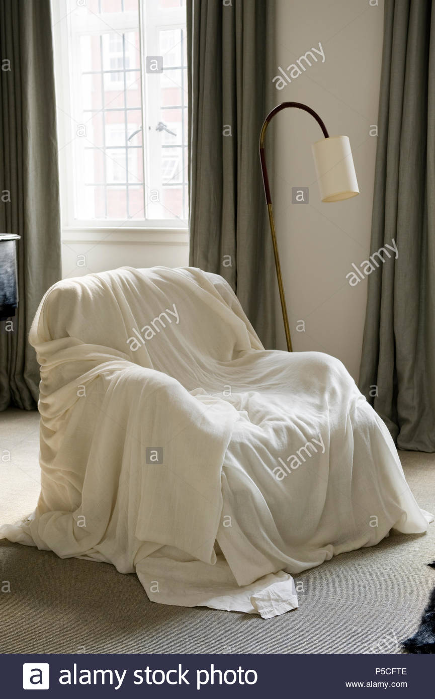 Sheet over armchair - Stock Image