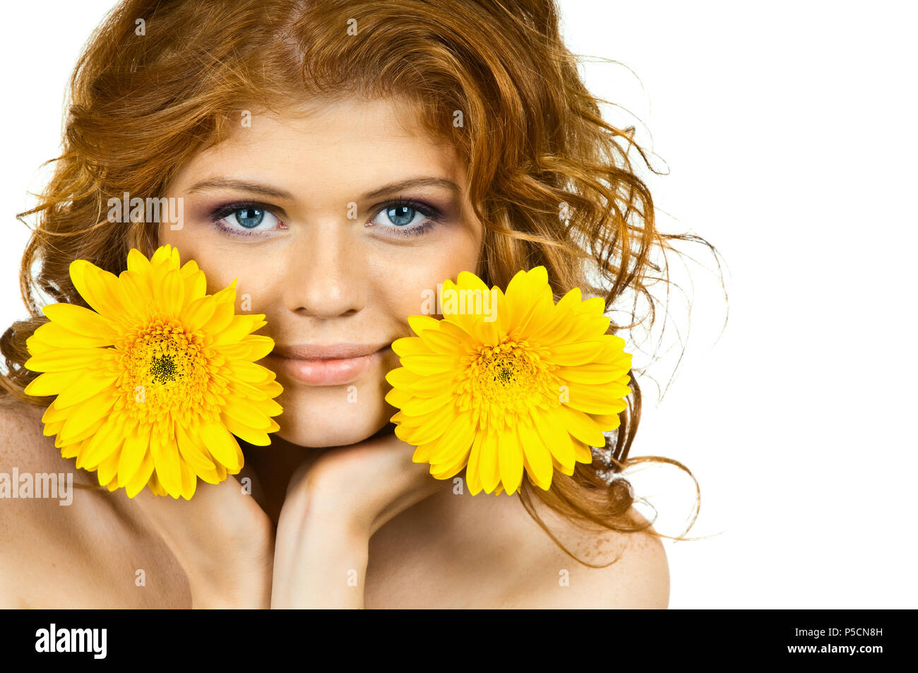 the very  pretty red-haired young woman  with yellow flowe, horizontal close up portrait - Stock Image