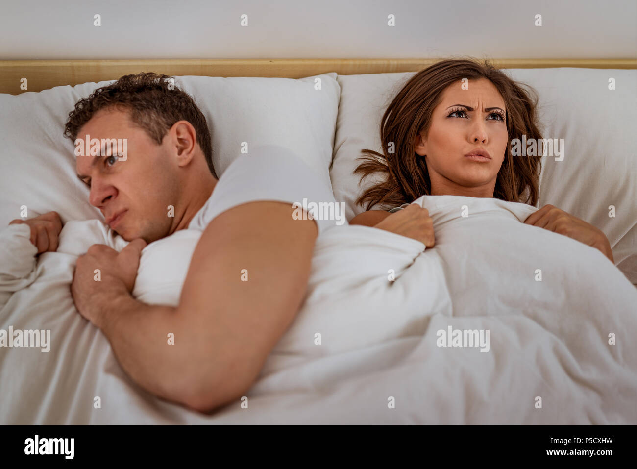 Young couple laying in bed with an expression of anger and displeased on their faces. - Stock Image