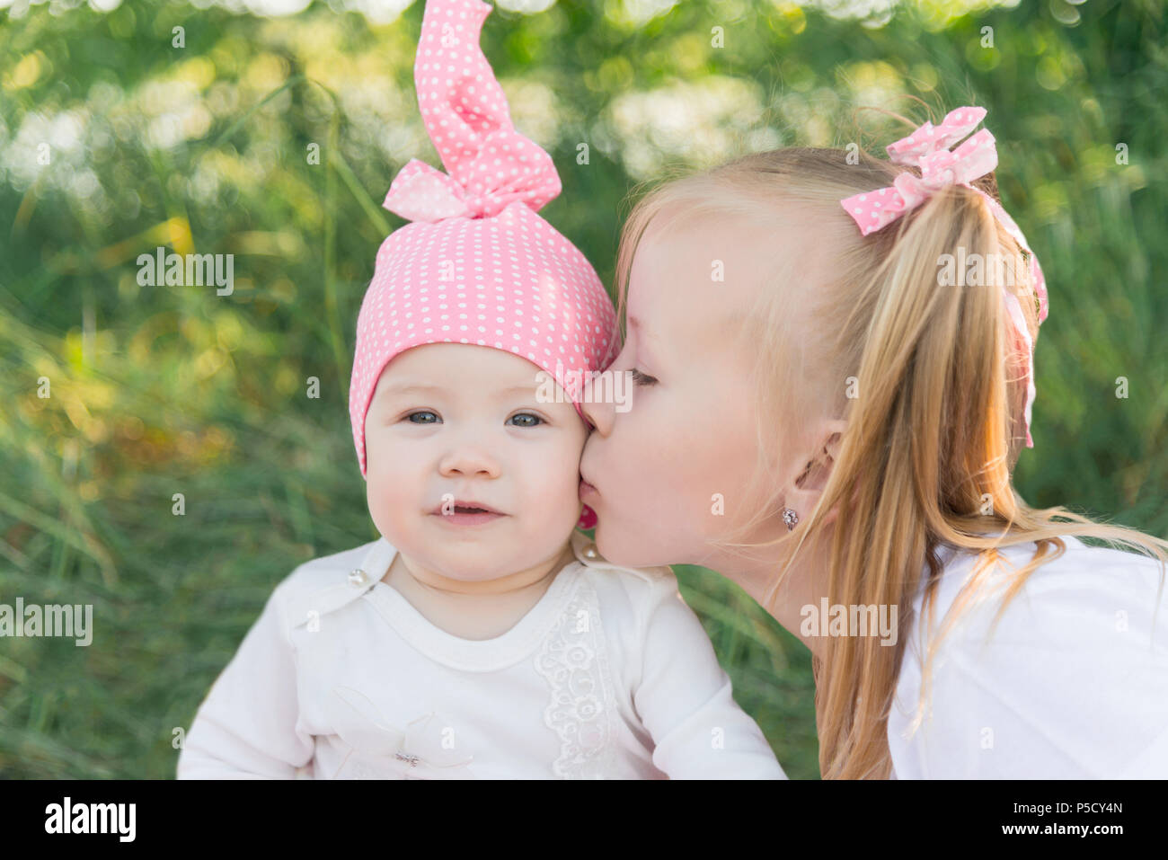 Two sisters. The older sister kisses the younger sister on the cheek. Pink hat in a pea and bows. - Stock Image