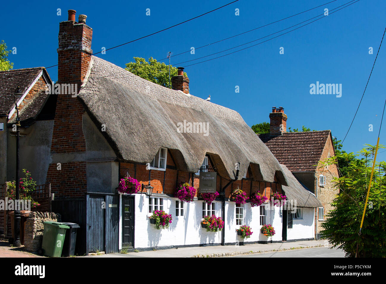 The Plough Inn on Church Street, West Hanney, Wantage, Oxfordshire, UK with a stunning display of flowers in hanging baskets on a bright summers day, - Stock Image