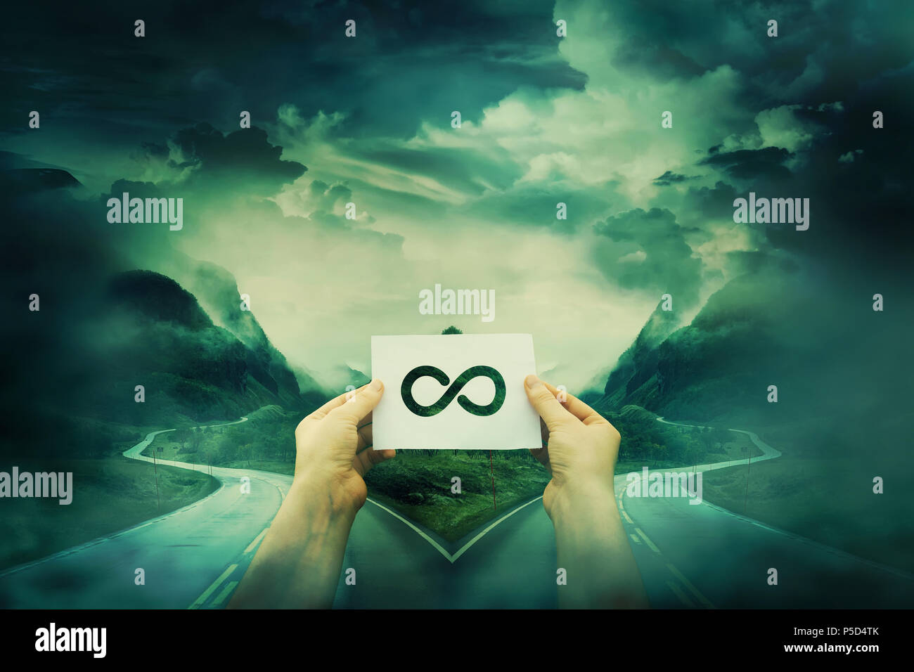 Hands holding a sheet with infinite sign in front of a crossroad, fork junction where road is splitted in two different ways. The infinity choice in l - Stock Image