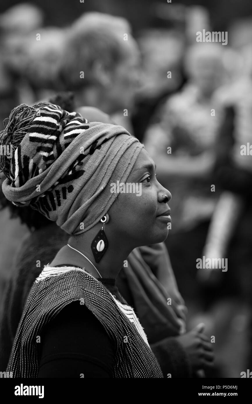 Candid Monochrome image of a beautiful black woman with Afro hairwrap at the 2018 Africa Oye music festival in Sefton Park, Liverpool. - Stock Image