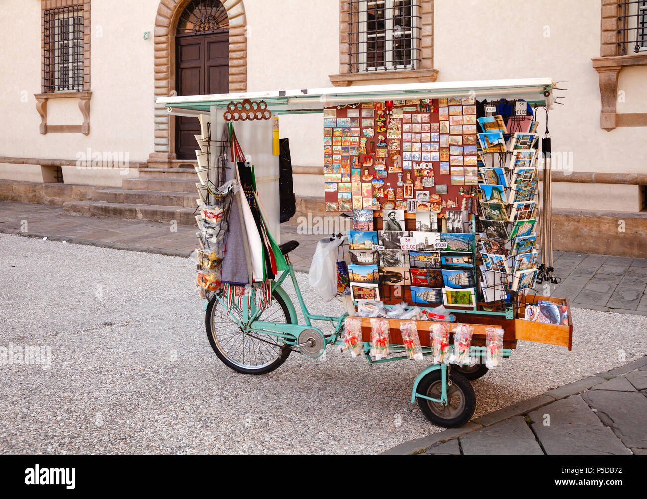 LUCCA, ITALY - MAY 31, 2018: Souvenir Stall on a Bicycle with fridge magnets  souvenirs and postcards for sale on a street - Stock Image
