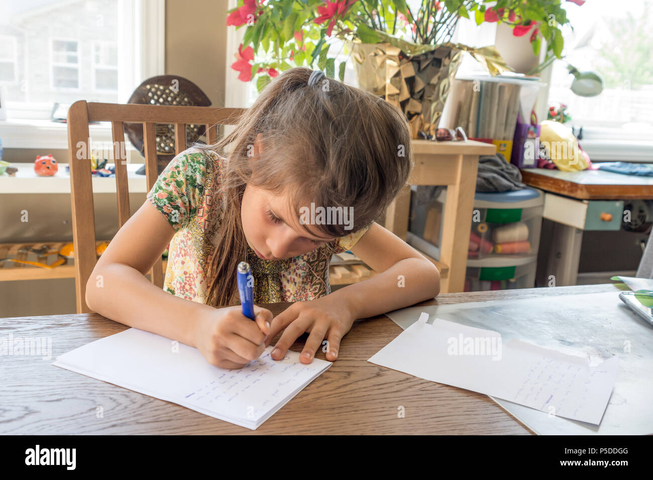 A girl writes and a letter on a white sheet of paper with a ballpoint pen - Stock Image