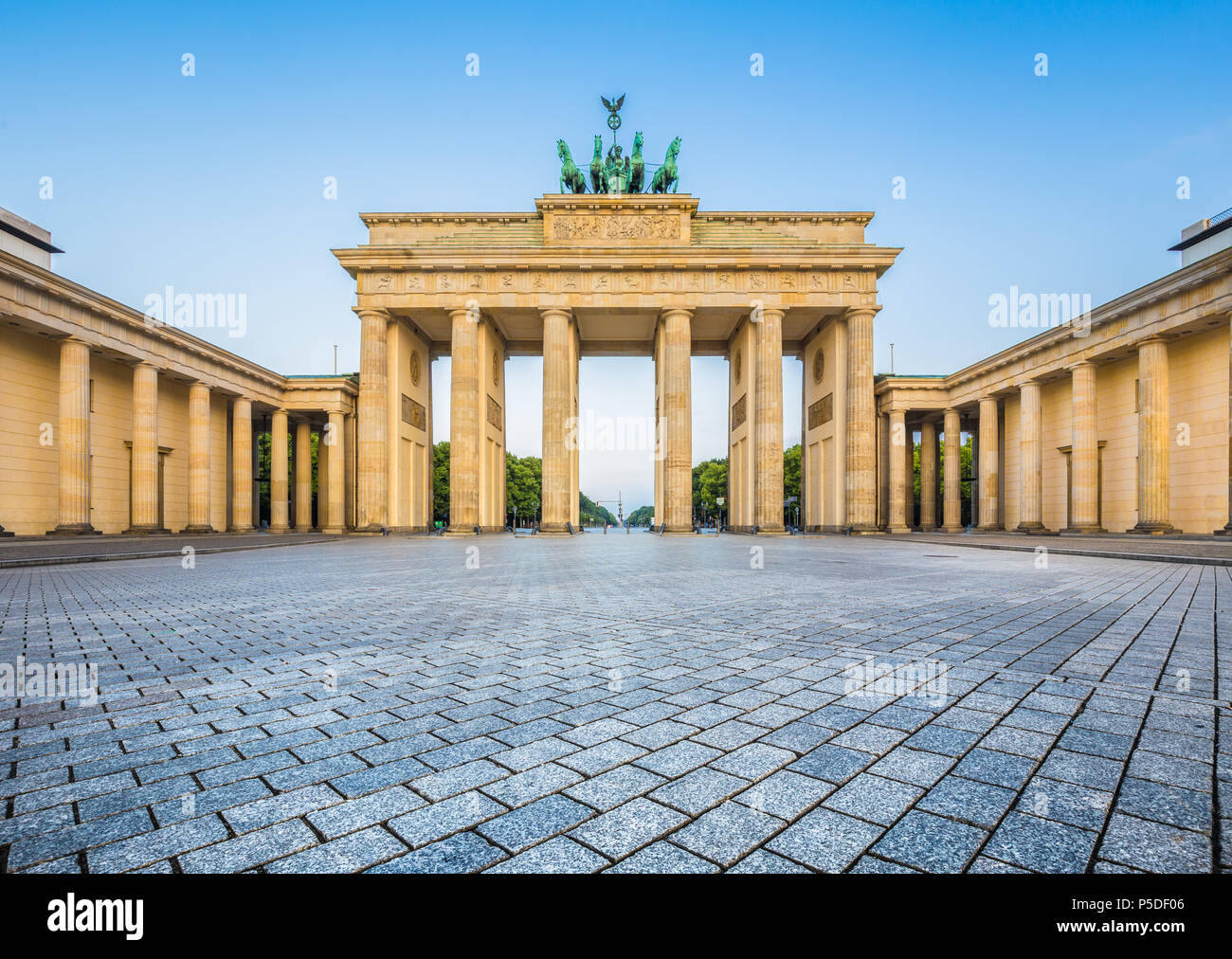 Famous Brandenburger Tor (Brandenburg Gate), one of the best-known landmarks and national symbols of Germany, in beautiful golden morning light at sun - Stock Image