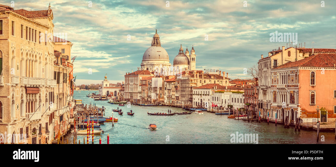 Classic panoramic view of famous Canal Grande with scenic Basilica di Santa Maria della Salute in beautiful golden evening light at sunset with retro  - Stock Image