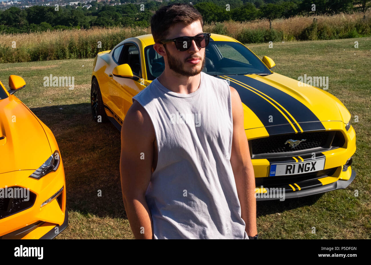 Muscular Young Man Poses With 2 European Ford Mustang 5 Litre V8