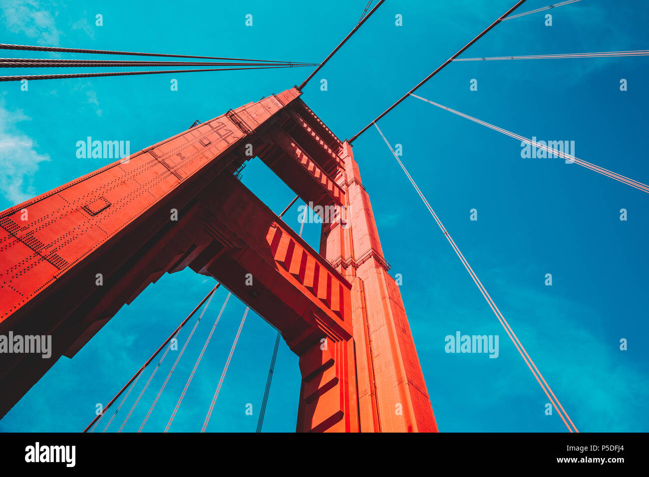 Beautiful low angle view of famous Golden Gate Bridge with blue sky and clouds on a sunny day in summer with retro vintage post crocessing filter effe - Stock Image