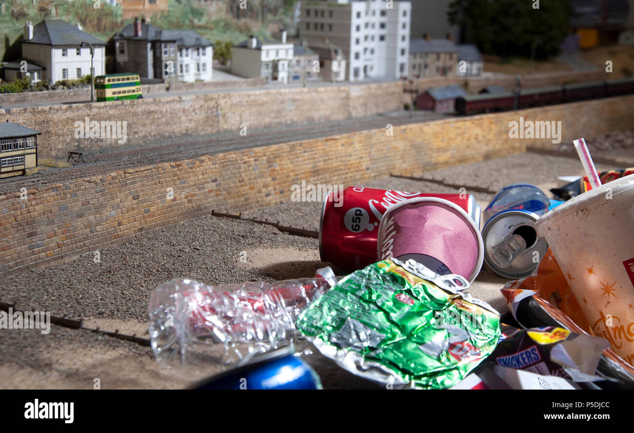 A play on scale showing the representation of the damage human waste has on the environment and Marine life. - Stock Image