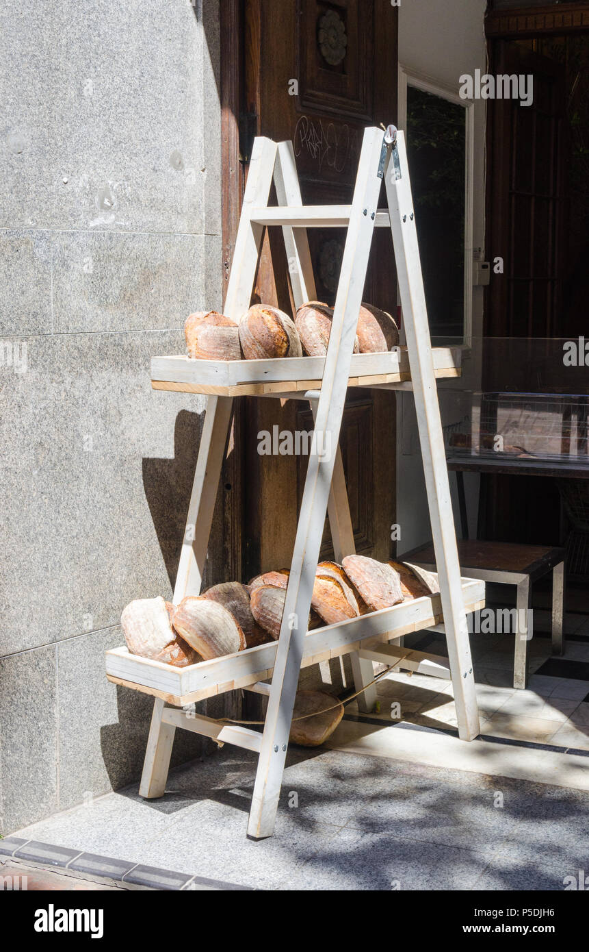 Loaves of artisan bread on wooden shelve outside a bakery in Birmingham city centre - Stock Image