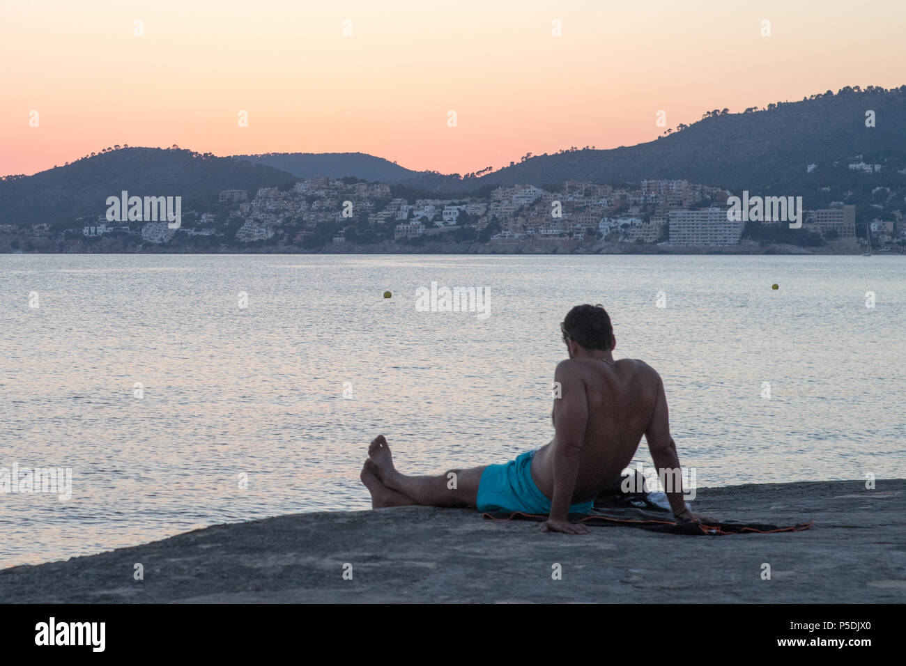 Man looking outside the sunset on sea Mallorca Spain - Stock Image