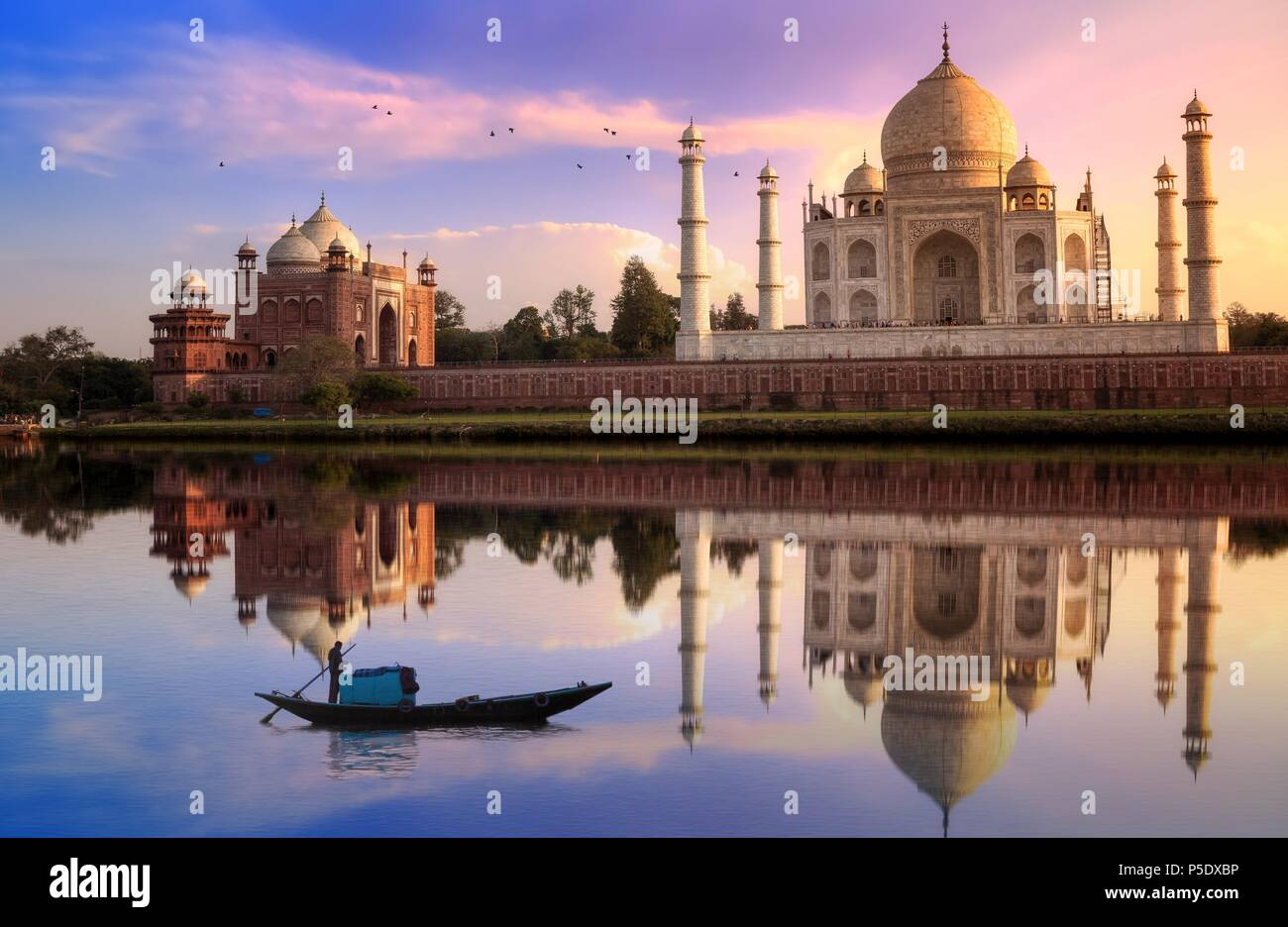 Taj Mahal Agra at sunset with moody sky with wooden boat on river Yamuna - Stock Image
